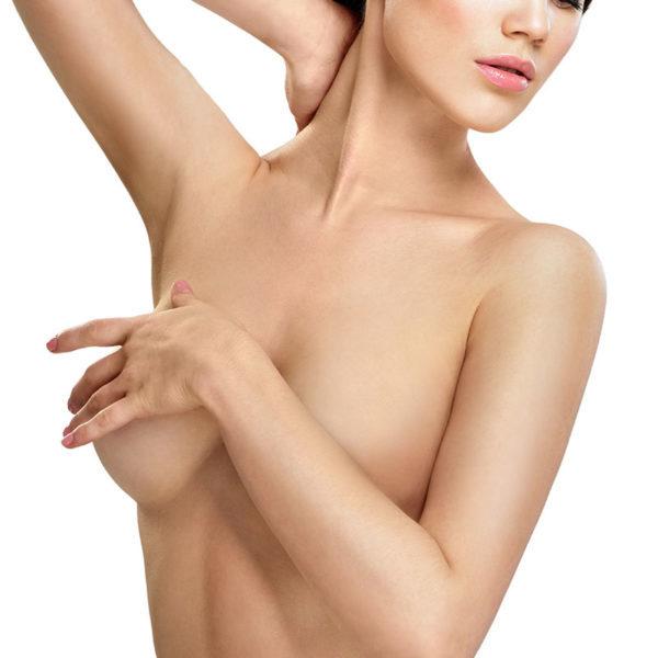 Eine sinnliche nackte, nach unten schauende Frau, die ihre Brüste mit ihren Händen bedeckt